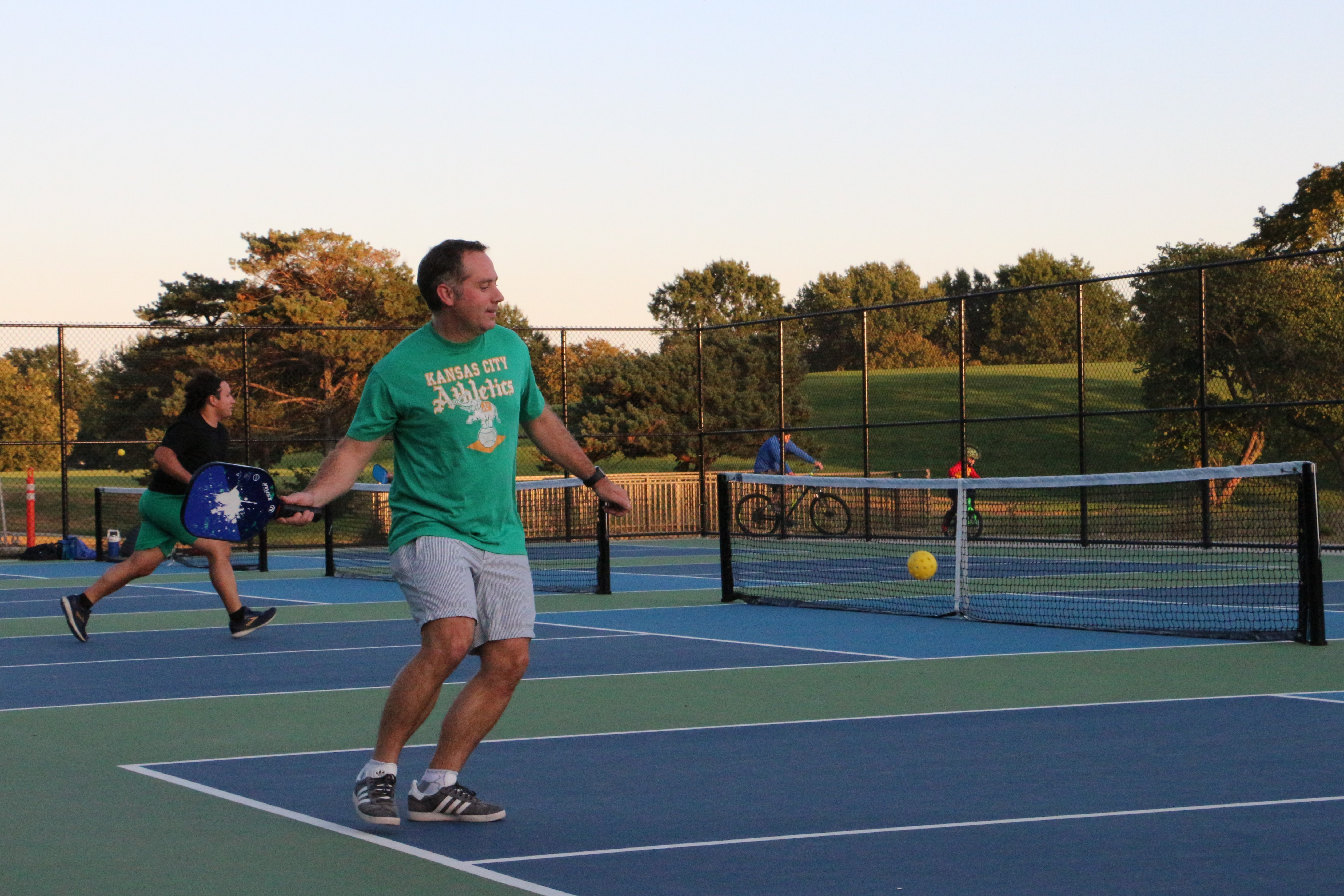 man playing pickleball on outdoor courts in a park