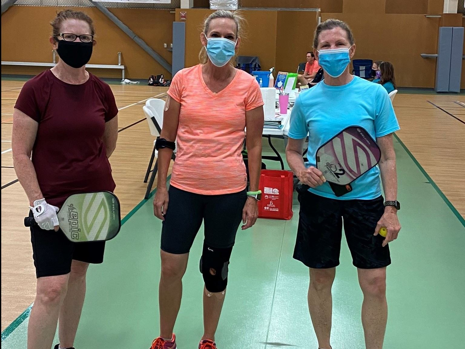 Masked pickleball players wait for match at tournament