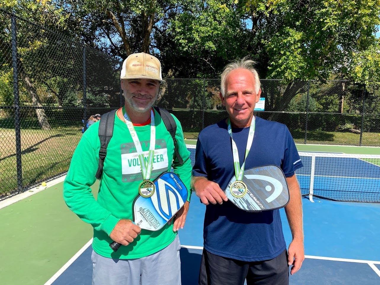 Man in green shirt and man in blue shirt holding pickleball paddles and displaying their medals.