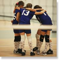 Female volleyball team in a huddle