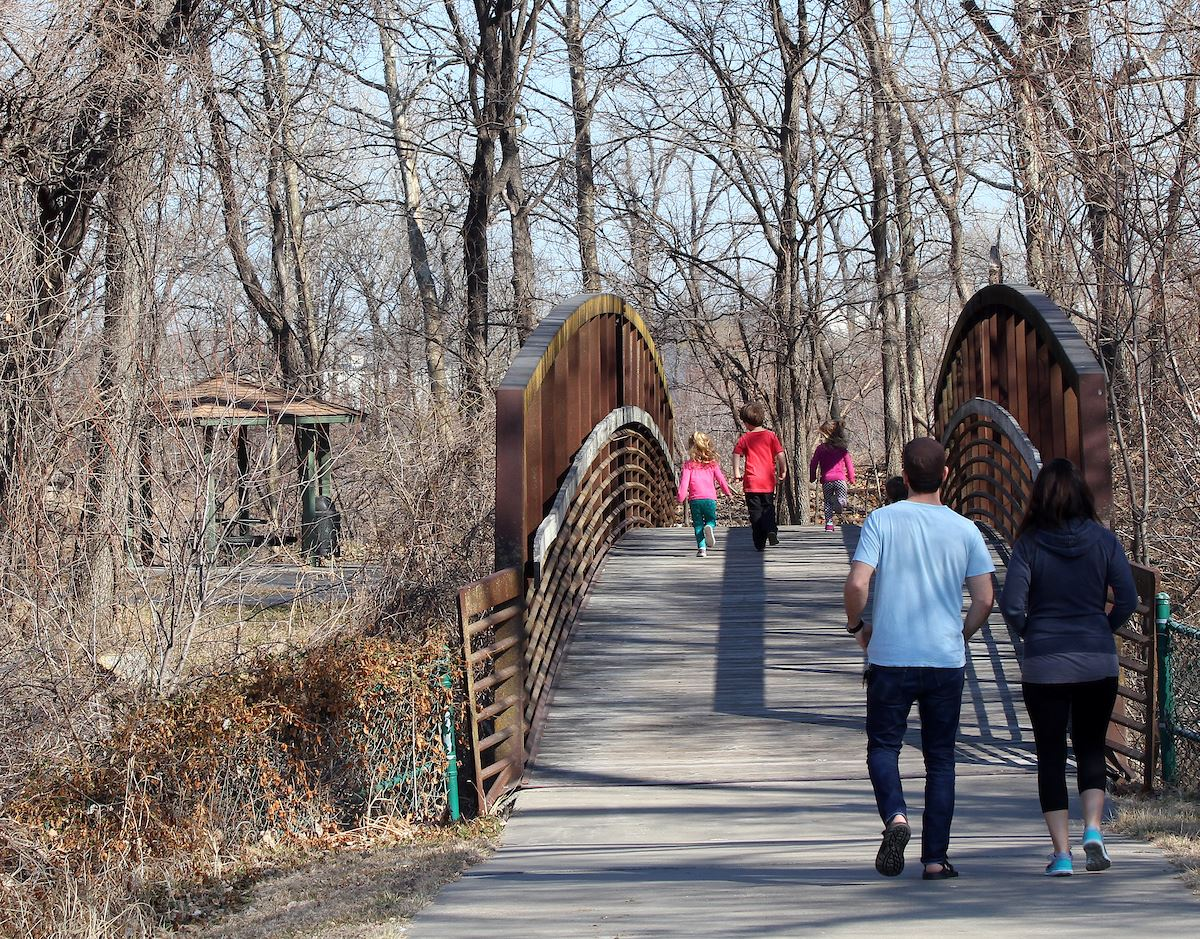People cross the bridge to Nelson Island, the northern terminus of the Mill Creek Streamway trail